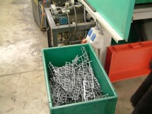 Plastic onderdelen vallen in een bak na productie.